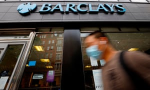 A pedestrian wearing a face mask walks past a branch of a Barclays bank
