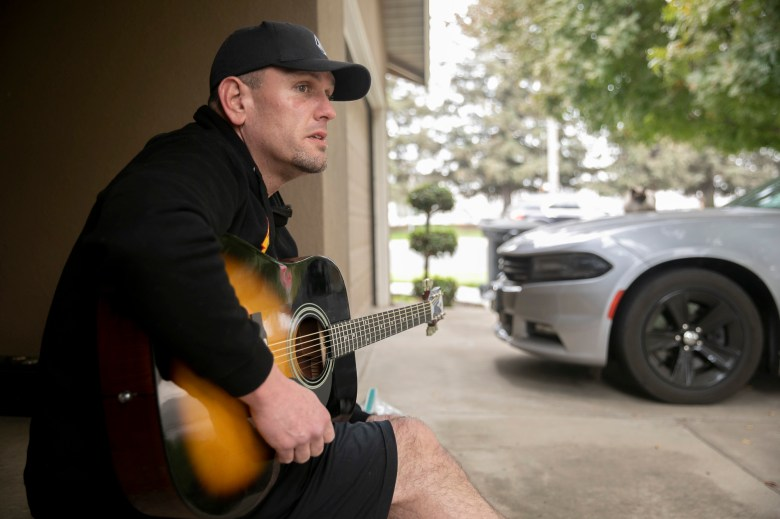Matt Hoffman, seen at his girlfriend's house in Escalon on Nov. 13, 2020, spends his days sitting on the porch while on hold with EDD, Bank of America and FEMA. According to Hoffman, he spends an average of 4 hours on hold per call. Photo by Anne Wernikoff for CalMatters