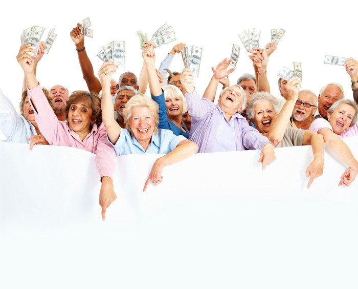 A group of elderly people holding wads of money in their hands and smiling.